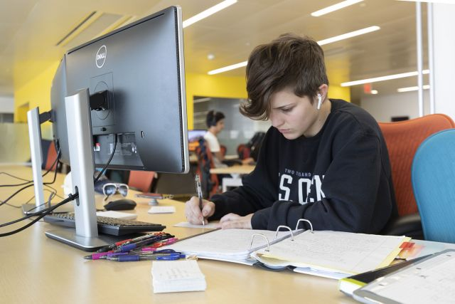Student working at a computer workstation with dual monitors and enough space on the desk for paper notes