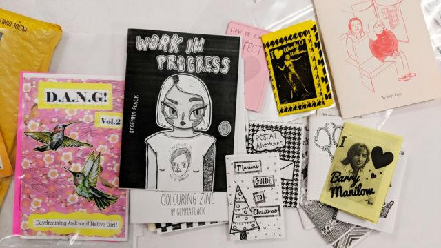 Selection of colorful zines, paper booklets, including Work in Progress and Senior Time
