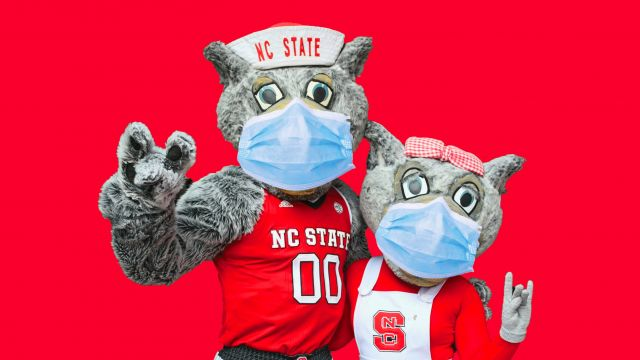 Mr and Ms Wuf posing in NC State outfits with face masks on