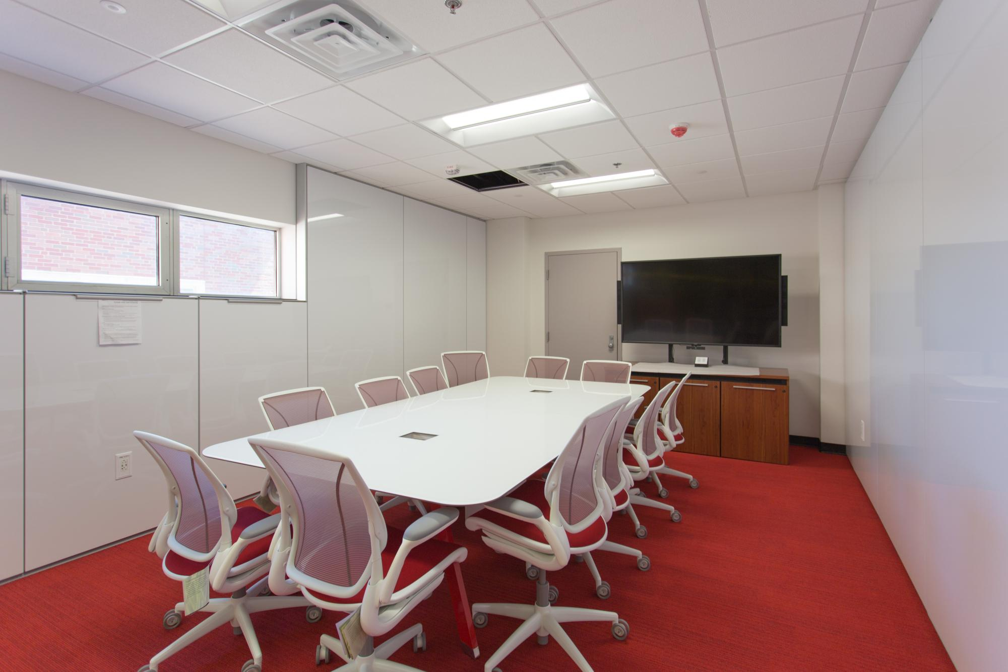 A room with a wall mounted screen, whiteboard wall, table and chairs