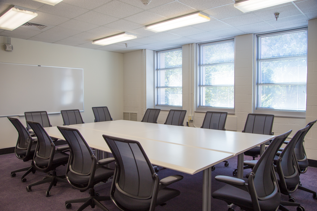 A conference table and fourteen chairs in a large room with three windows