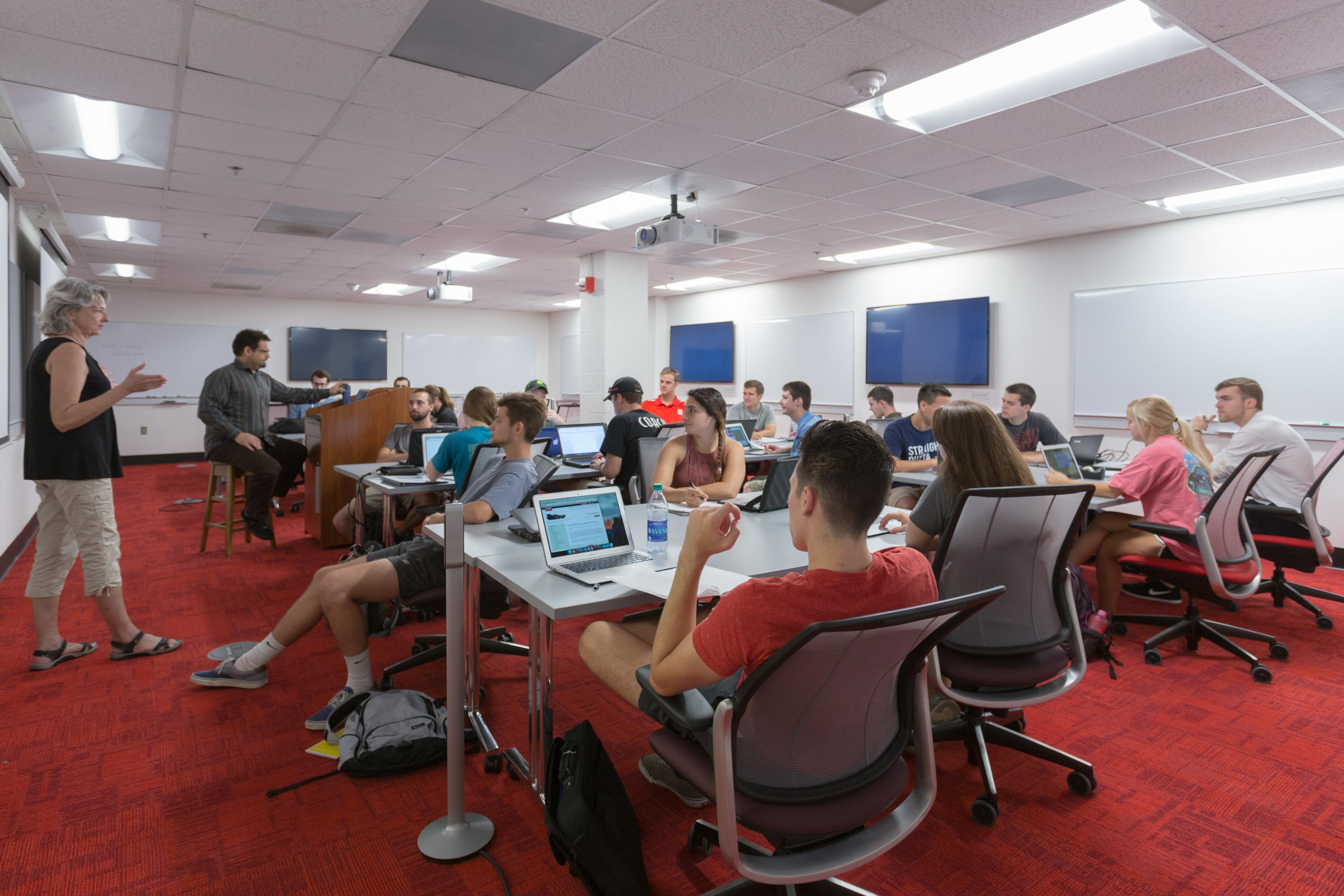 An instructor teaching students sitting at tables in ITTC Lab 2 at DH Hill