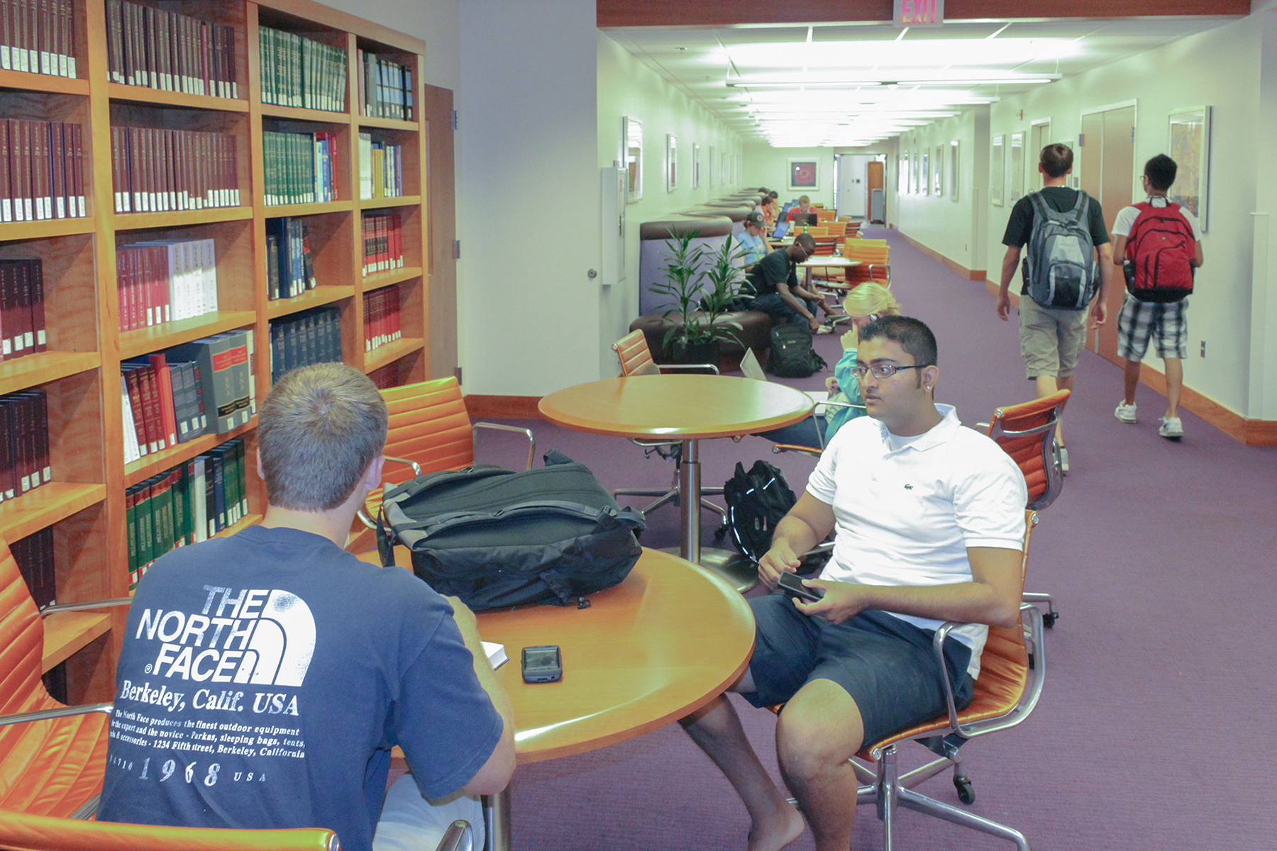 Two students sitting next to a wall of bookshelves, with several other tables in a row behind them