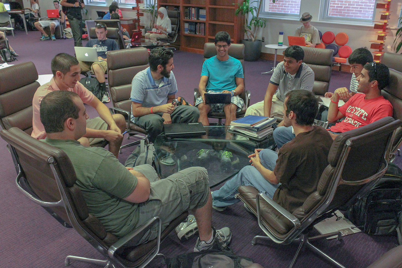 A group of students sitting around a low glass table in the learning commons at DH Hill