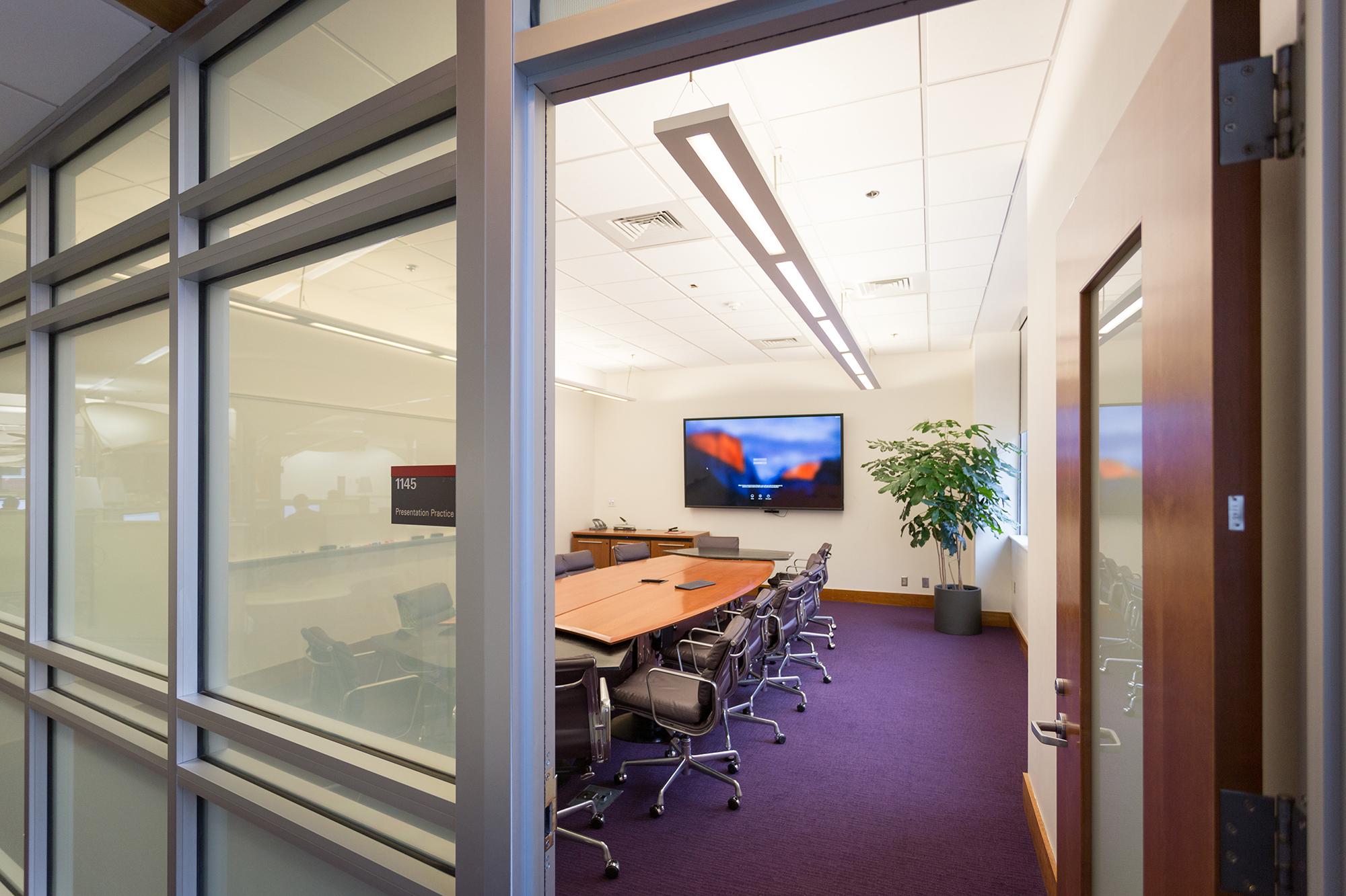 A presentation practice room at DH Hill with a wall mounted screen, table, and 10 chairs