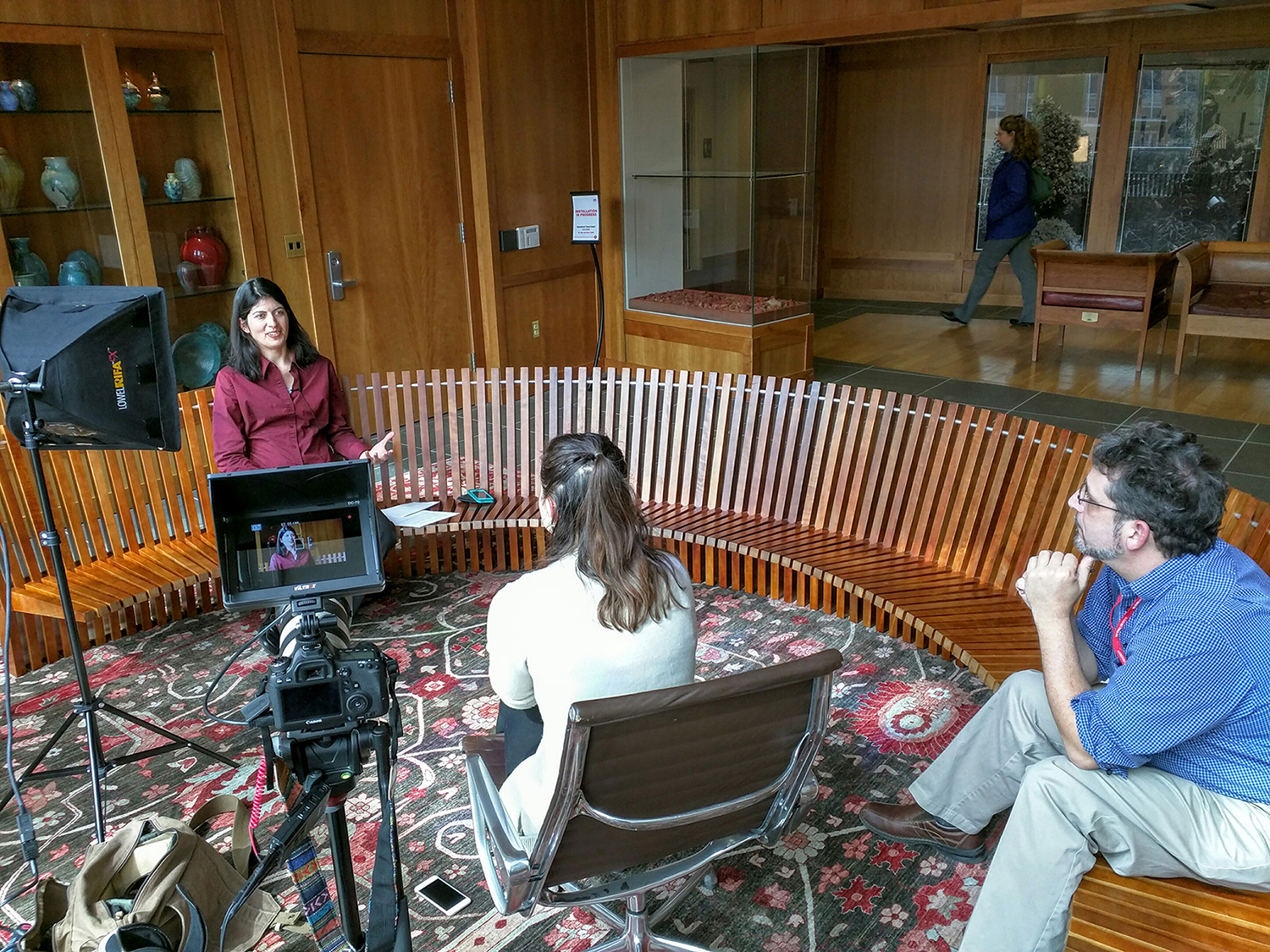 Students film a speaker sitting on a semicircular wooden bench