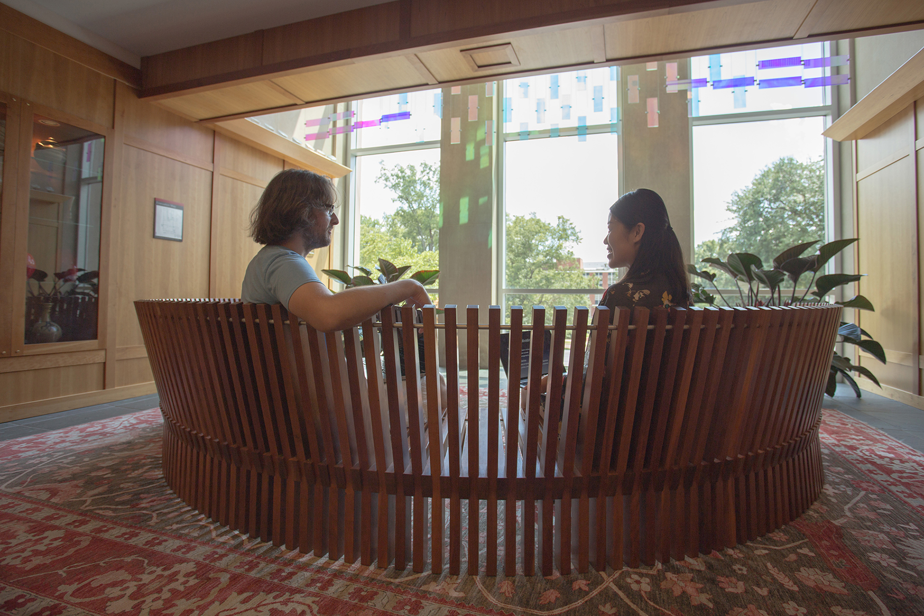 Students sit on a semicircular wooden bench in the conservatory at DH Hill Library