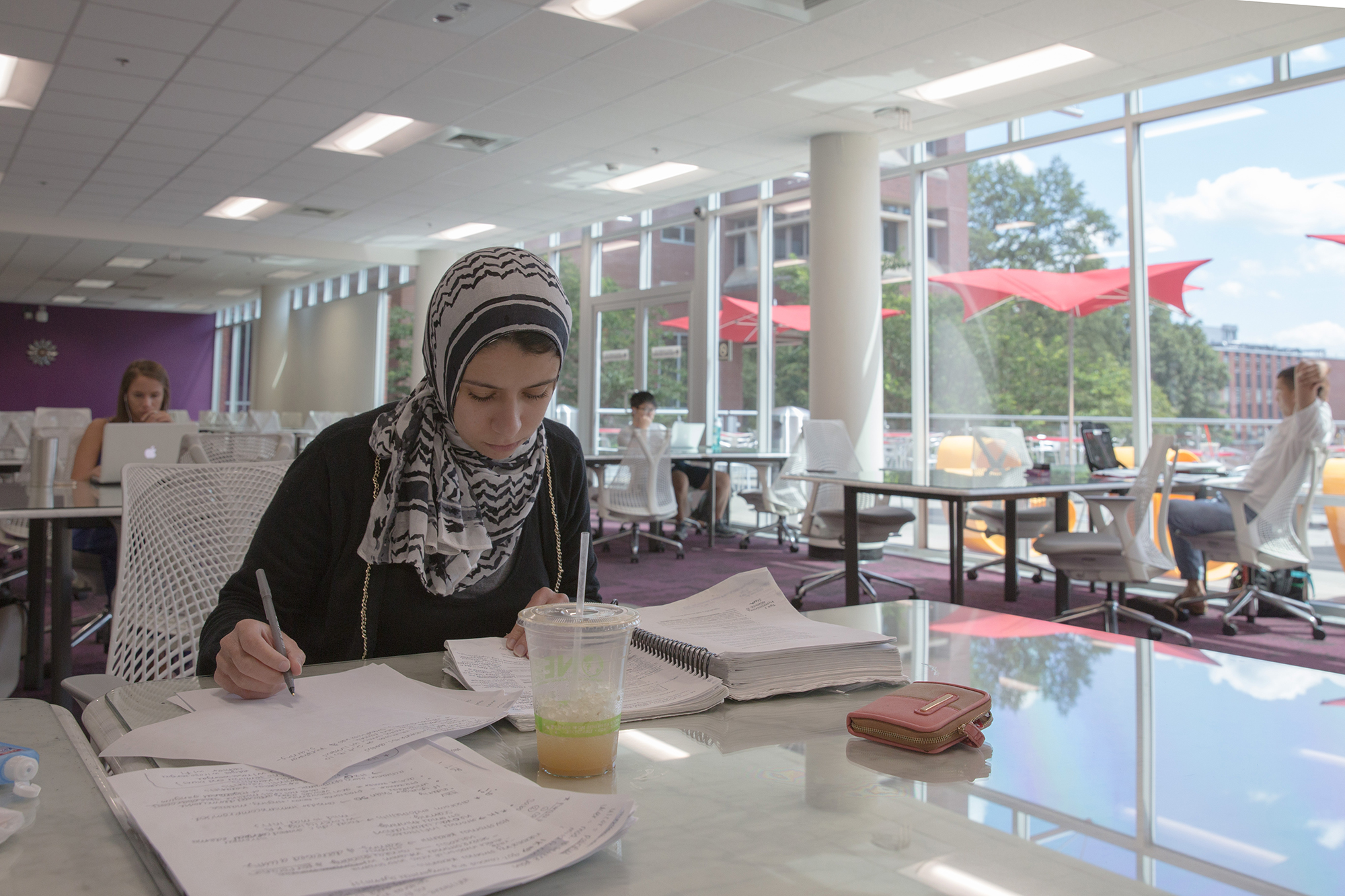A student writes in a notebook at a glasstopped table in the silent reading room at DH Hill Library