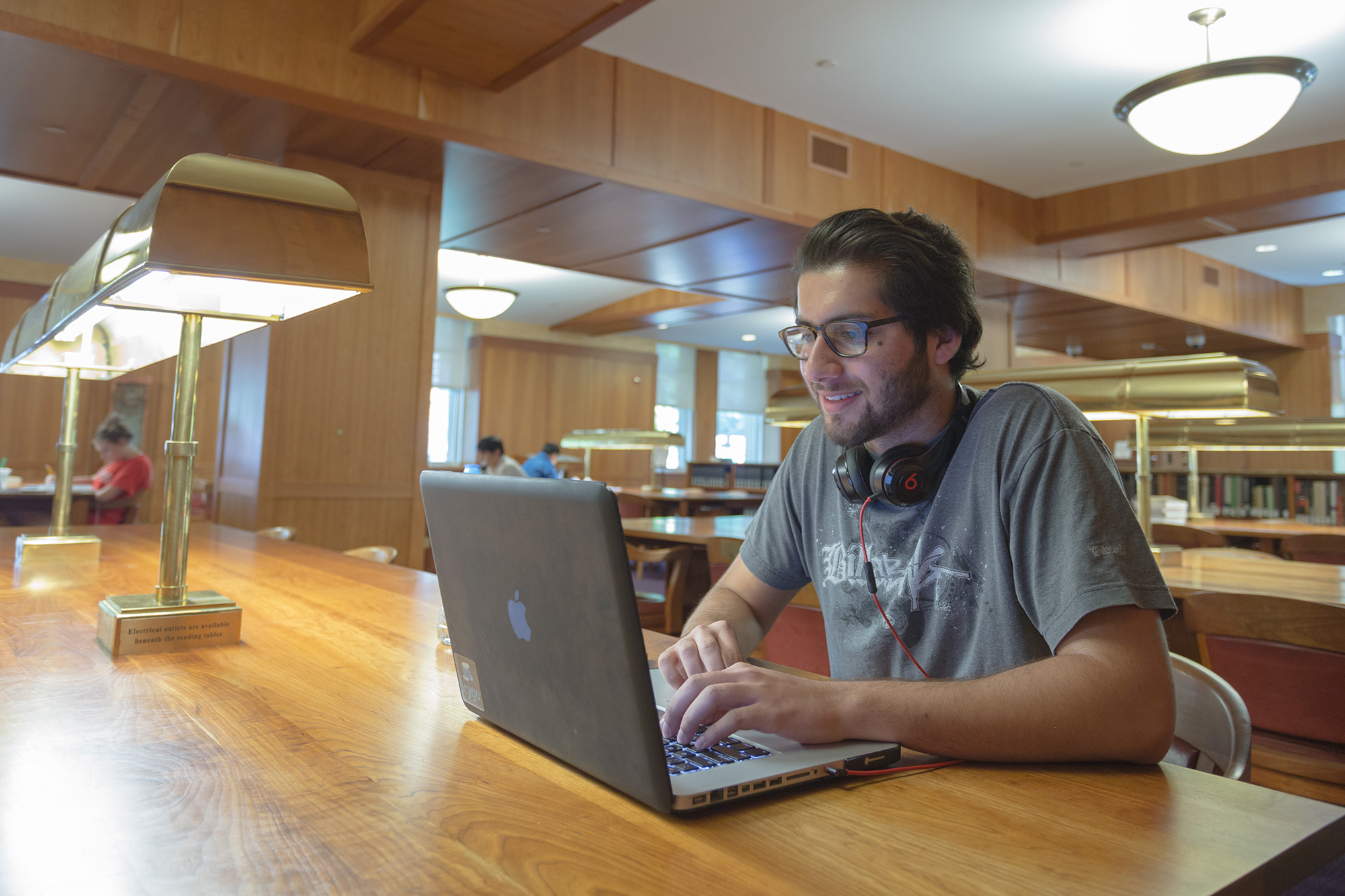 A student works at a laptop at a long wooden table