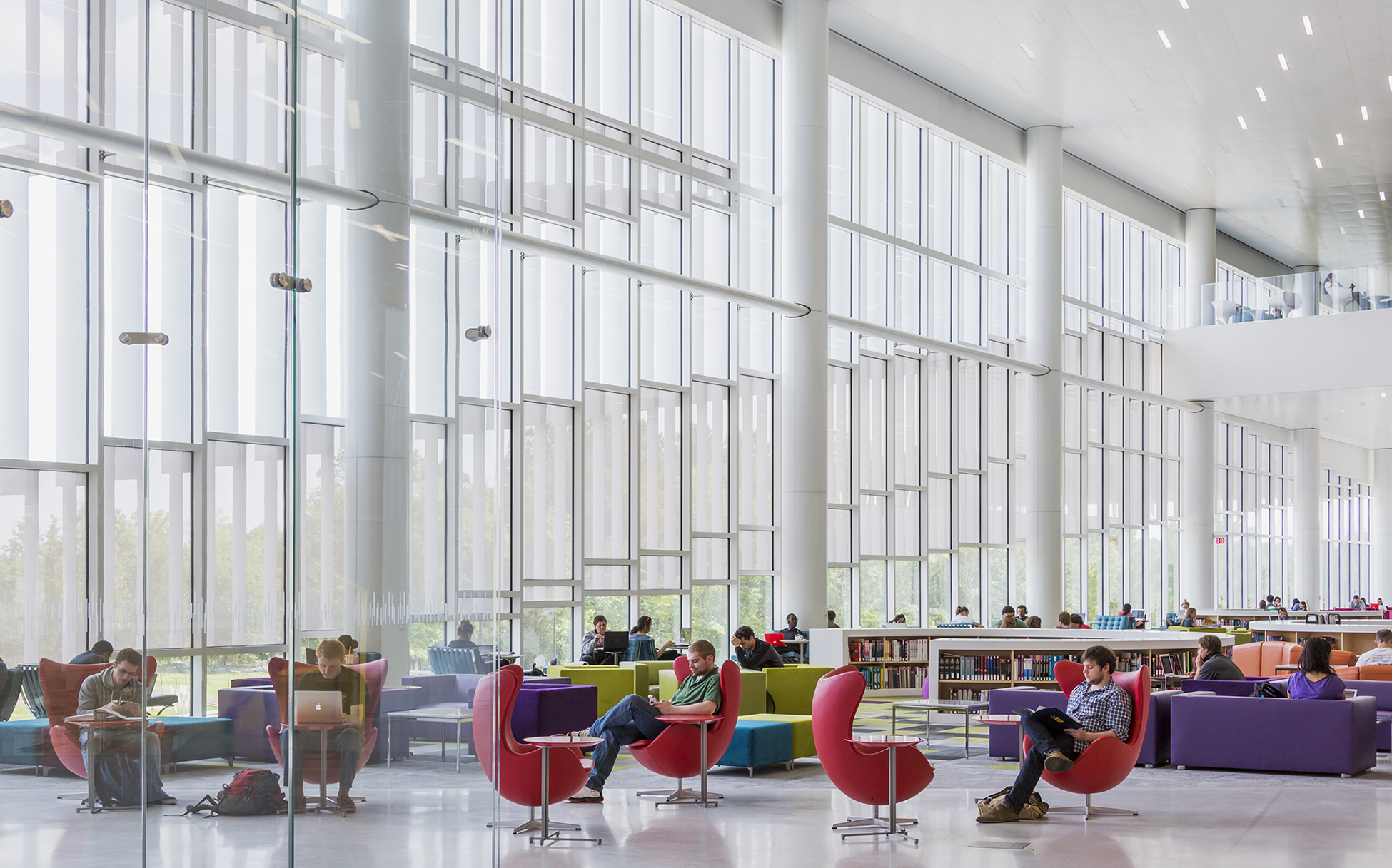 A huge open lobby, glass walled on one side, with colorful chairs and tables