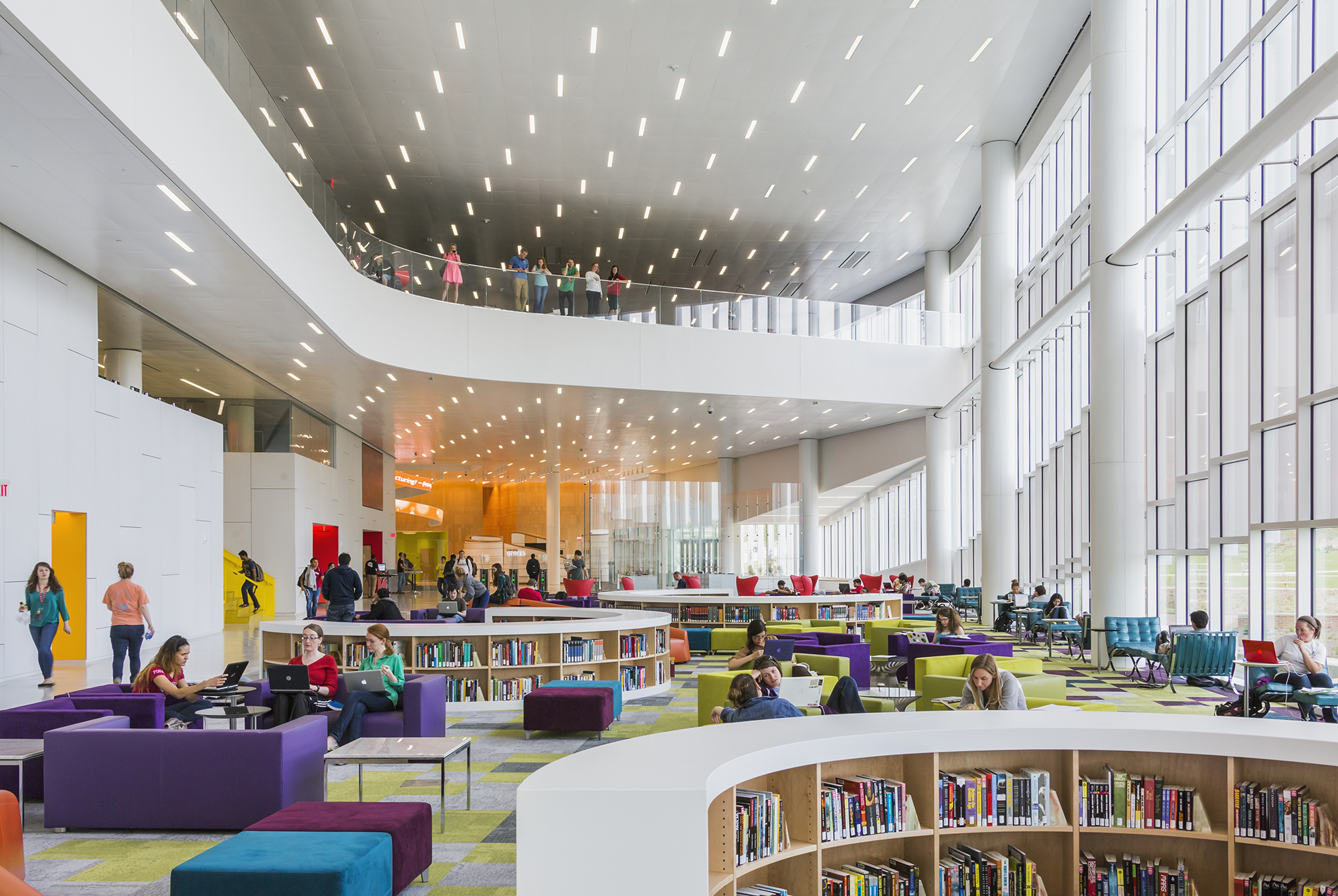 A huge open lobby, glass walled on one side, with colorful chairs and books