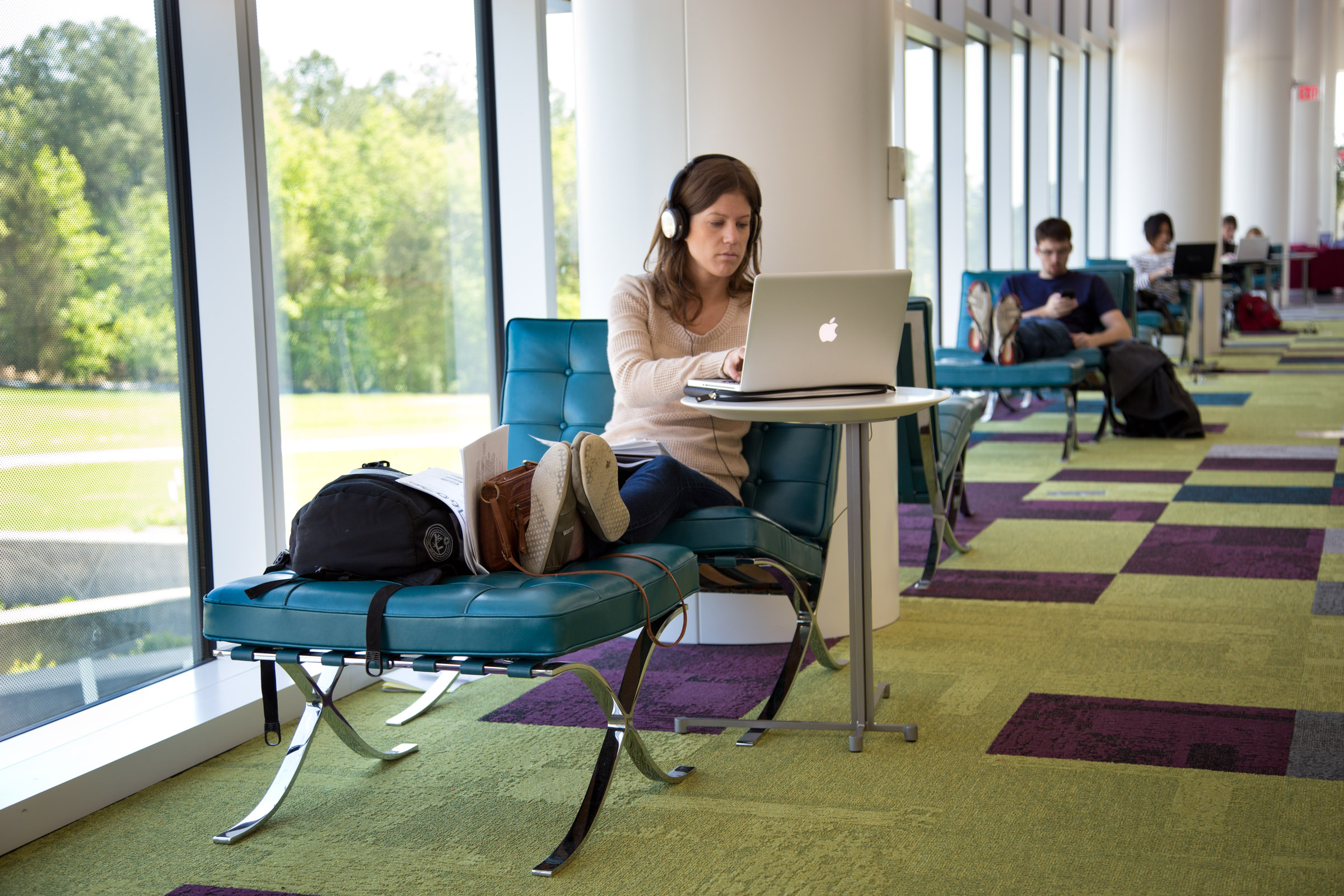 A student with their feet up on a stool next to a glass wall overlooking Centennial Campus