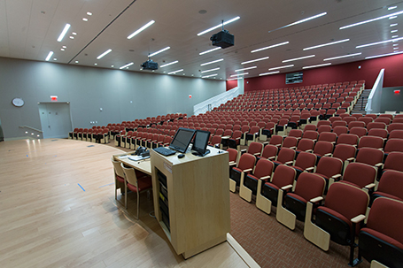 A large auditorium full of red seats with a projector and podium