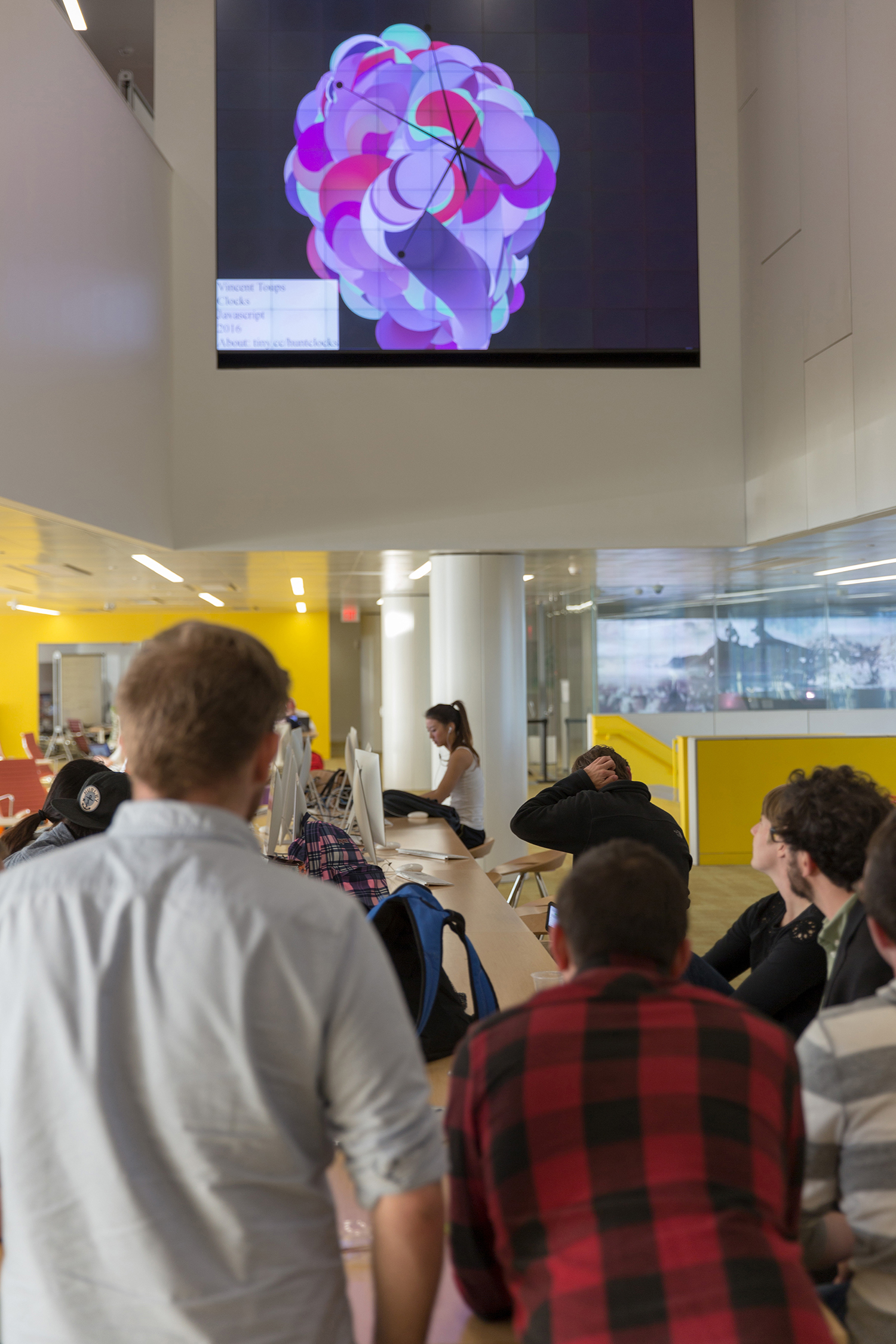 Students look at an image projected onto the wall of the commons at Hunt Library