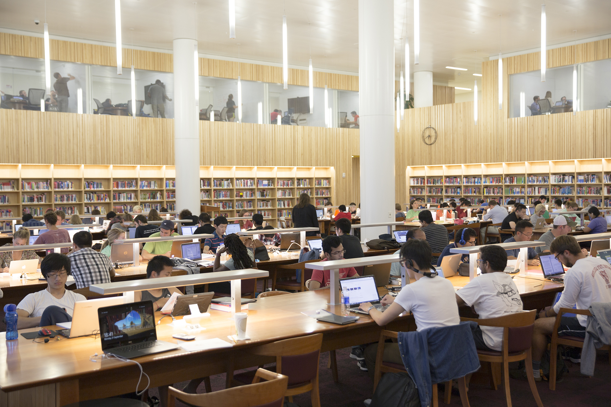 Students work at laptops at long wooden tables in the quiet reading room at Hunt Library