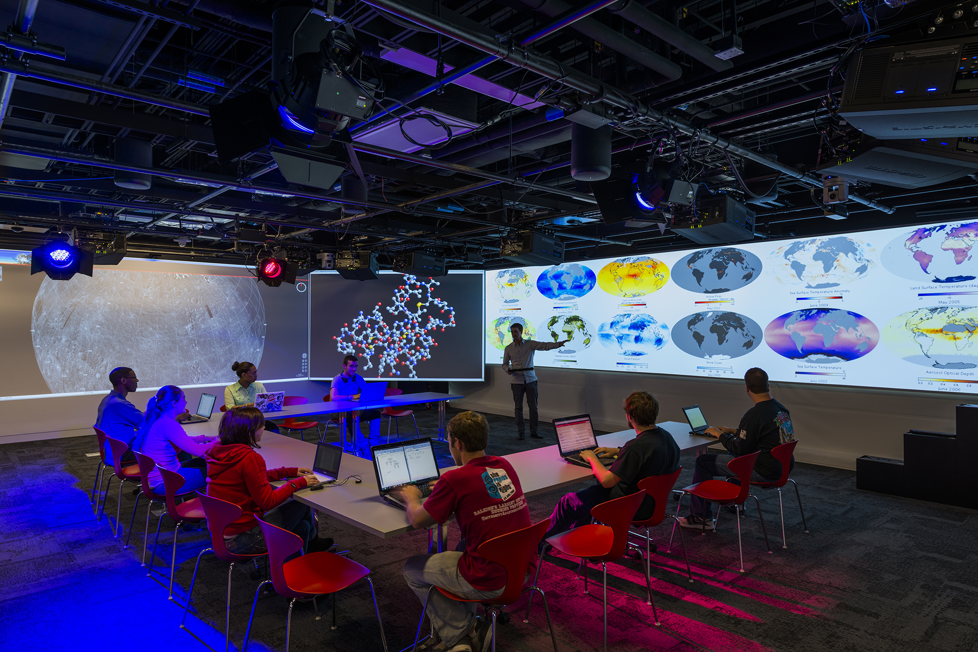An instructor gestures toward an image projected onto the walls of Hunt's teaching and visualization lab