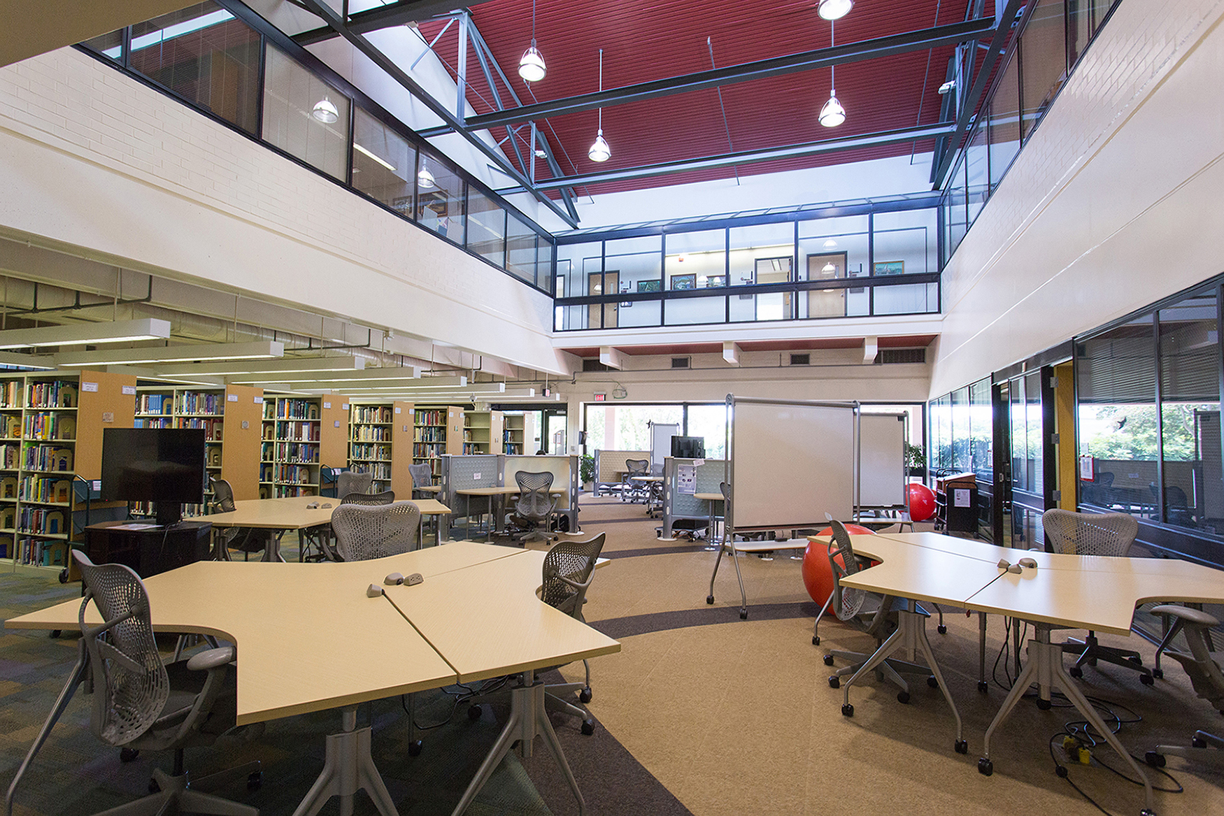 A reading room with bookstacks, desks, and whiteboards