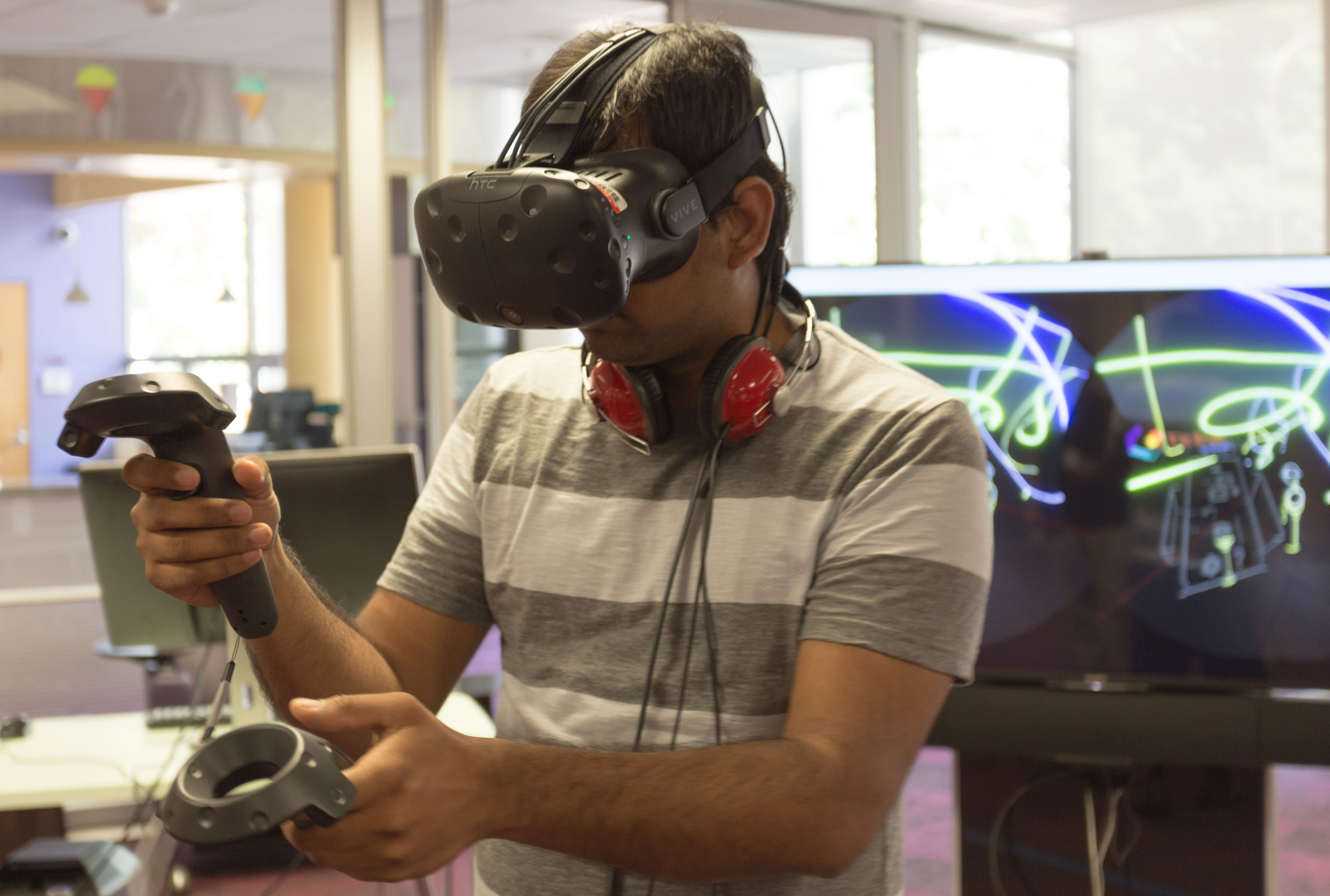 A student wearing a virtual reality headset with a screen display behind them