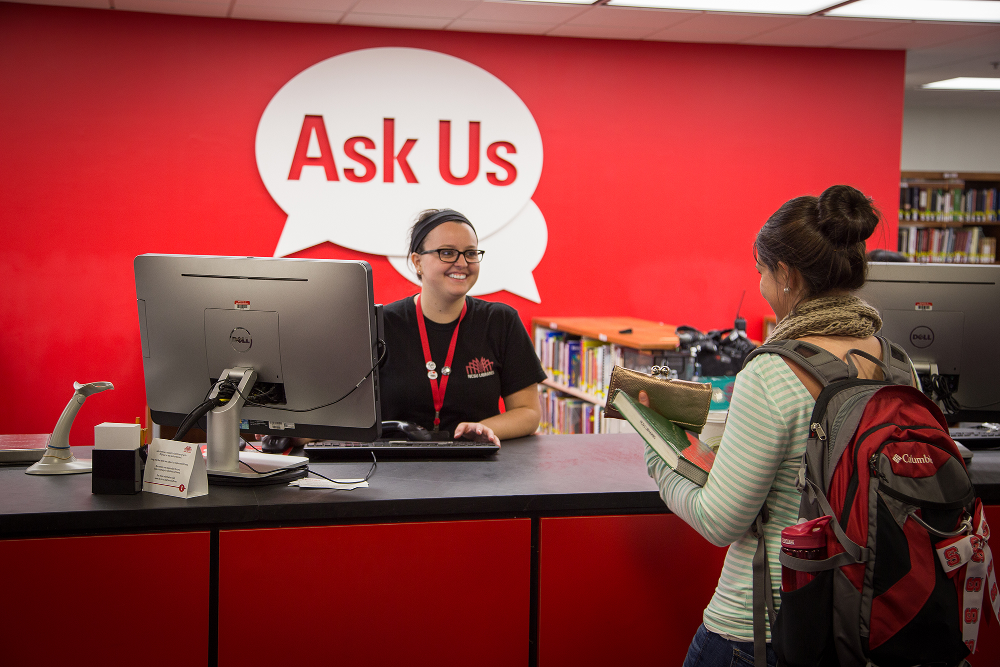 An employee helps a patron with a book at the Ask Us desk