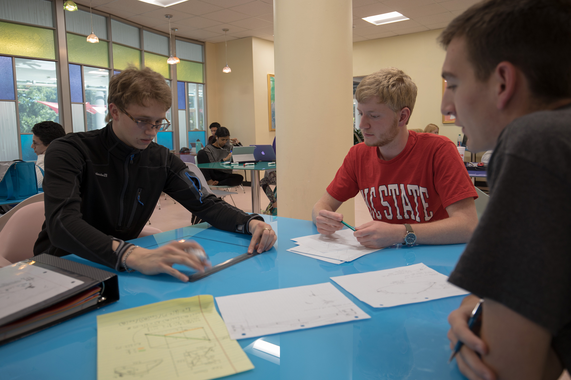 Three students using a ruler and papers at a table in the cone zone