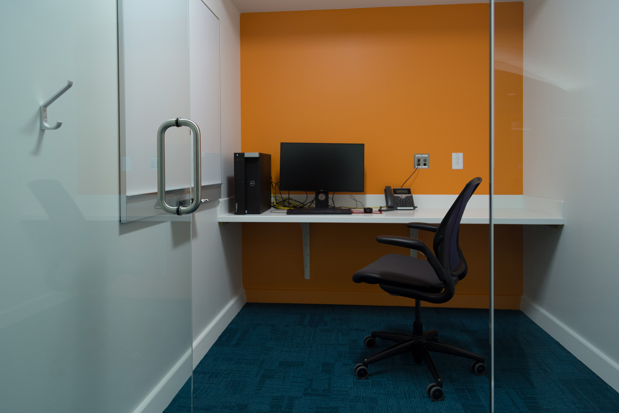 A small room with a desktop computer, telephone, desk, chair, and whiteboard