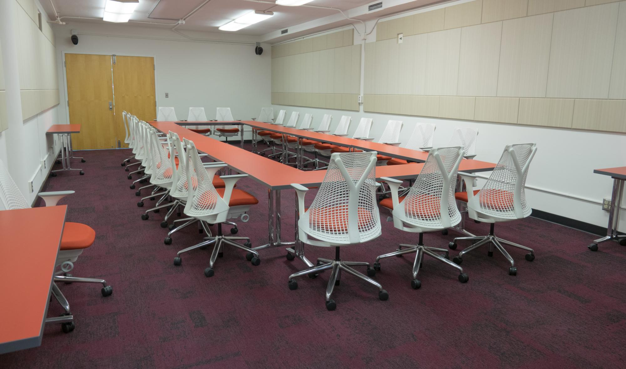 A large seminar room with tables arranged in a circle in the center