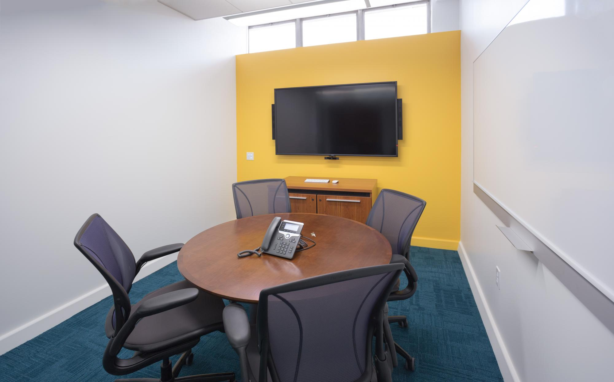 A room with a telephone, table, chairs, wall mounted screen, and whiteboard