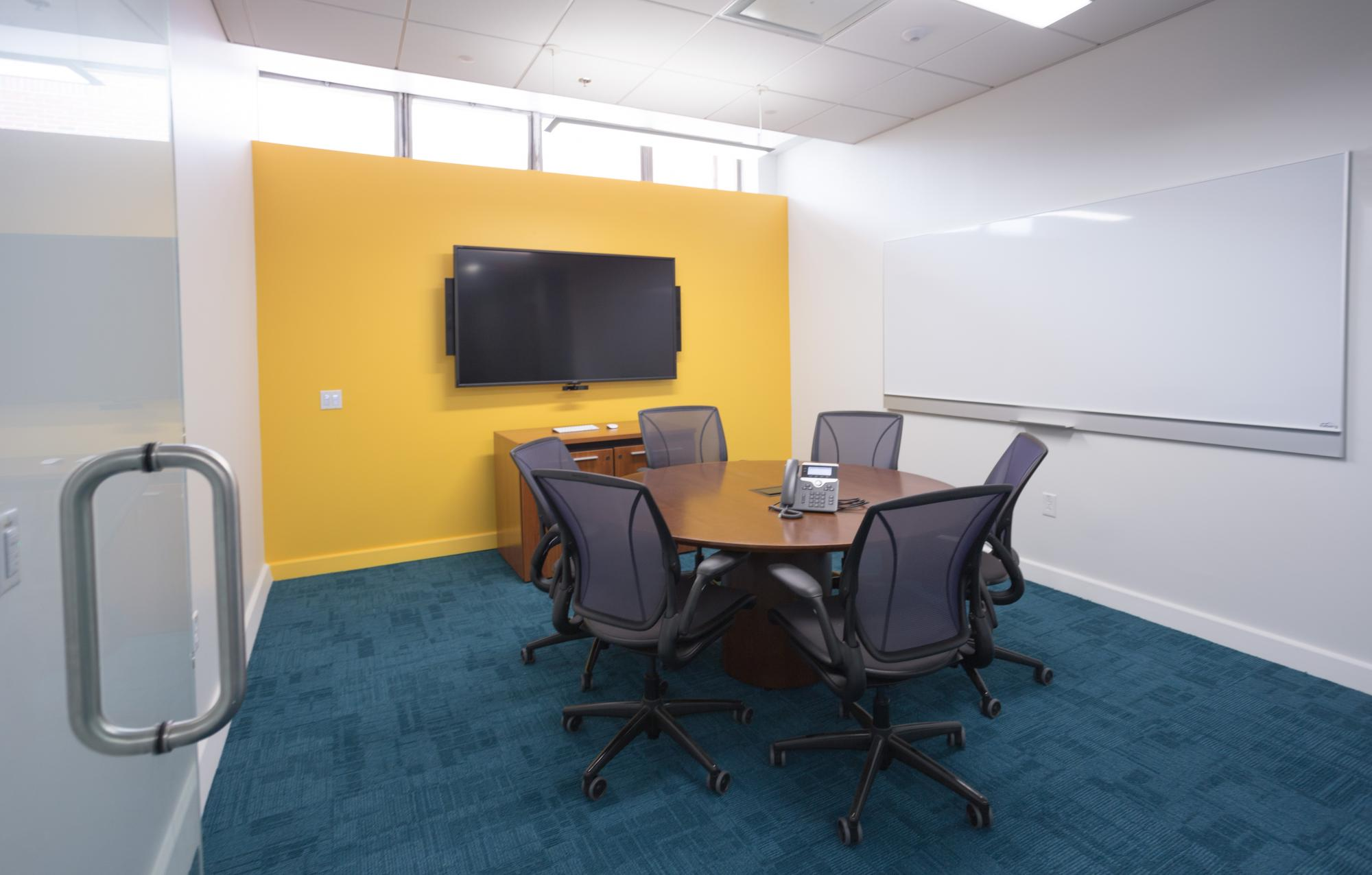 A faculty workroom with wall mounted screen, whiteboard, telephone, table and 6 chairs