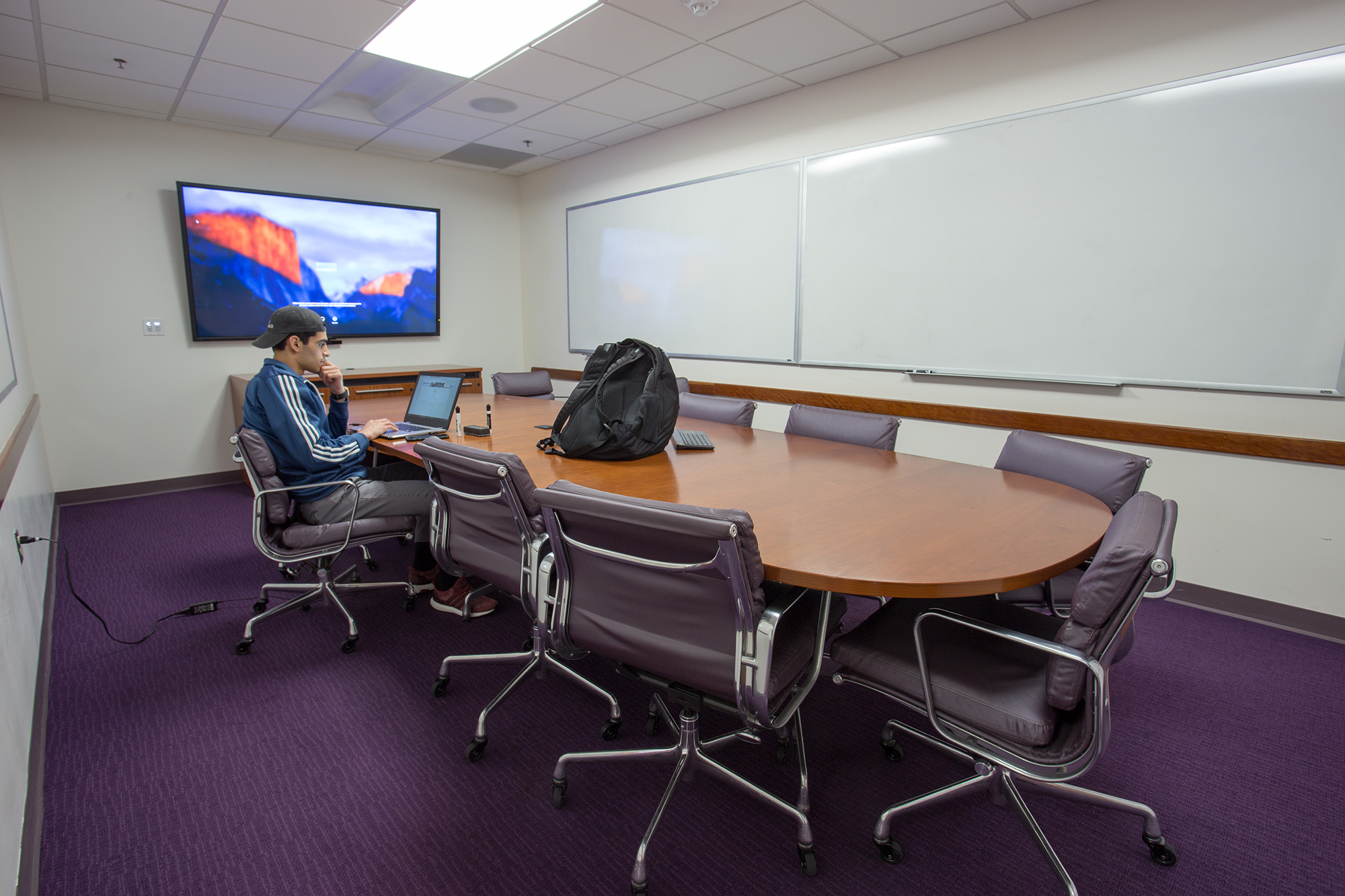 A student sitting at a long conference table working on a wall mounted display