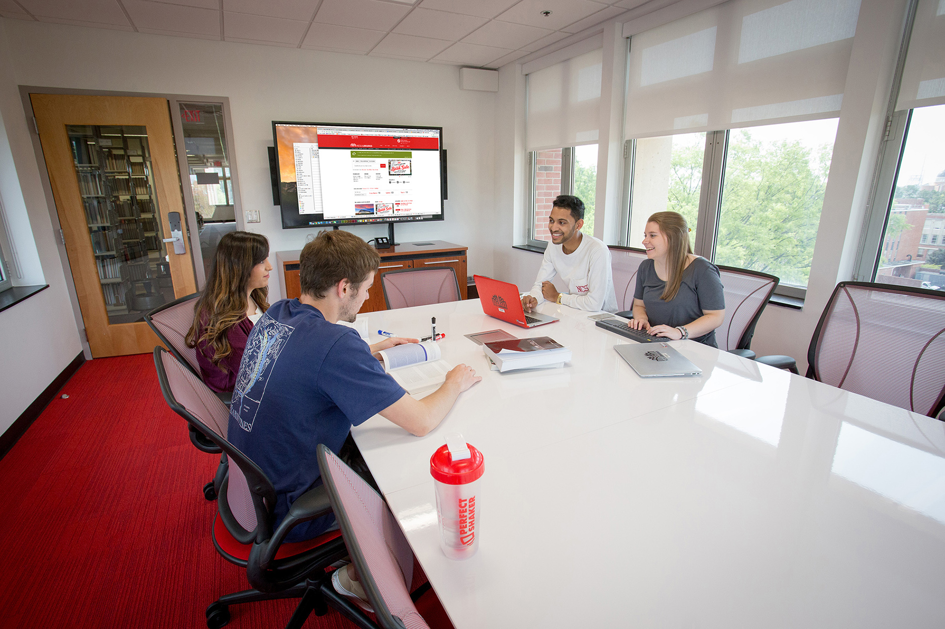 Students sitting at a long table in a graduate study room with a wall mounted screen at DH Hill