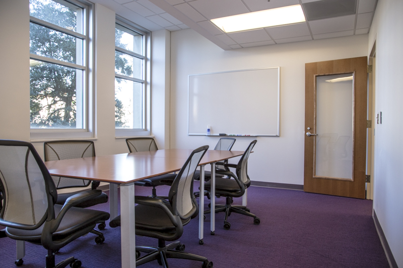 A graduate study room at DH Hill with a long table, whiteboard, and six chairs