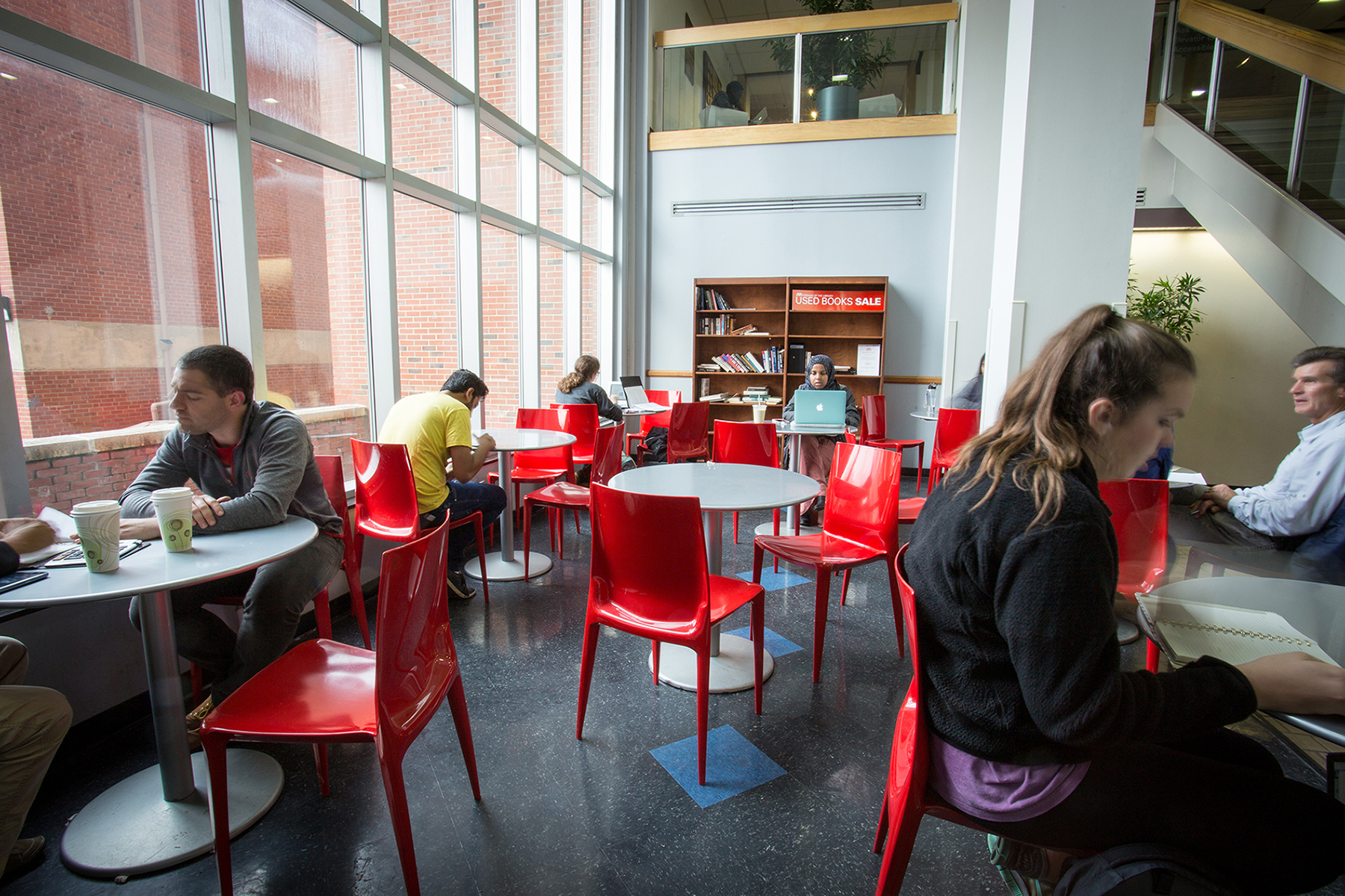 Students drinking coffee at tables in between a glass wall and a staircase