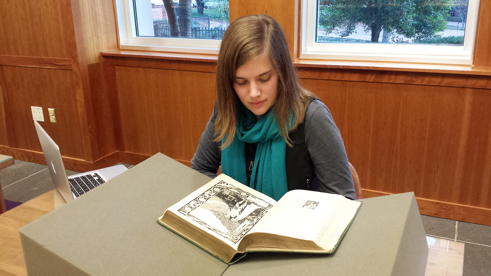 A student reading a book on a display stand in a wooden paneled room