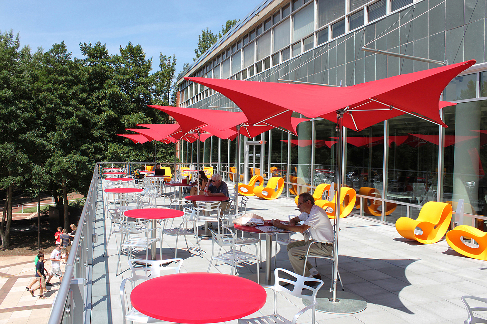 Students work at tables under umbrellas on the terrace at DH Hill Library