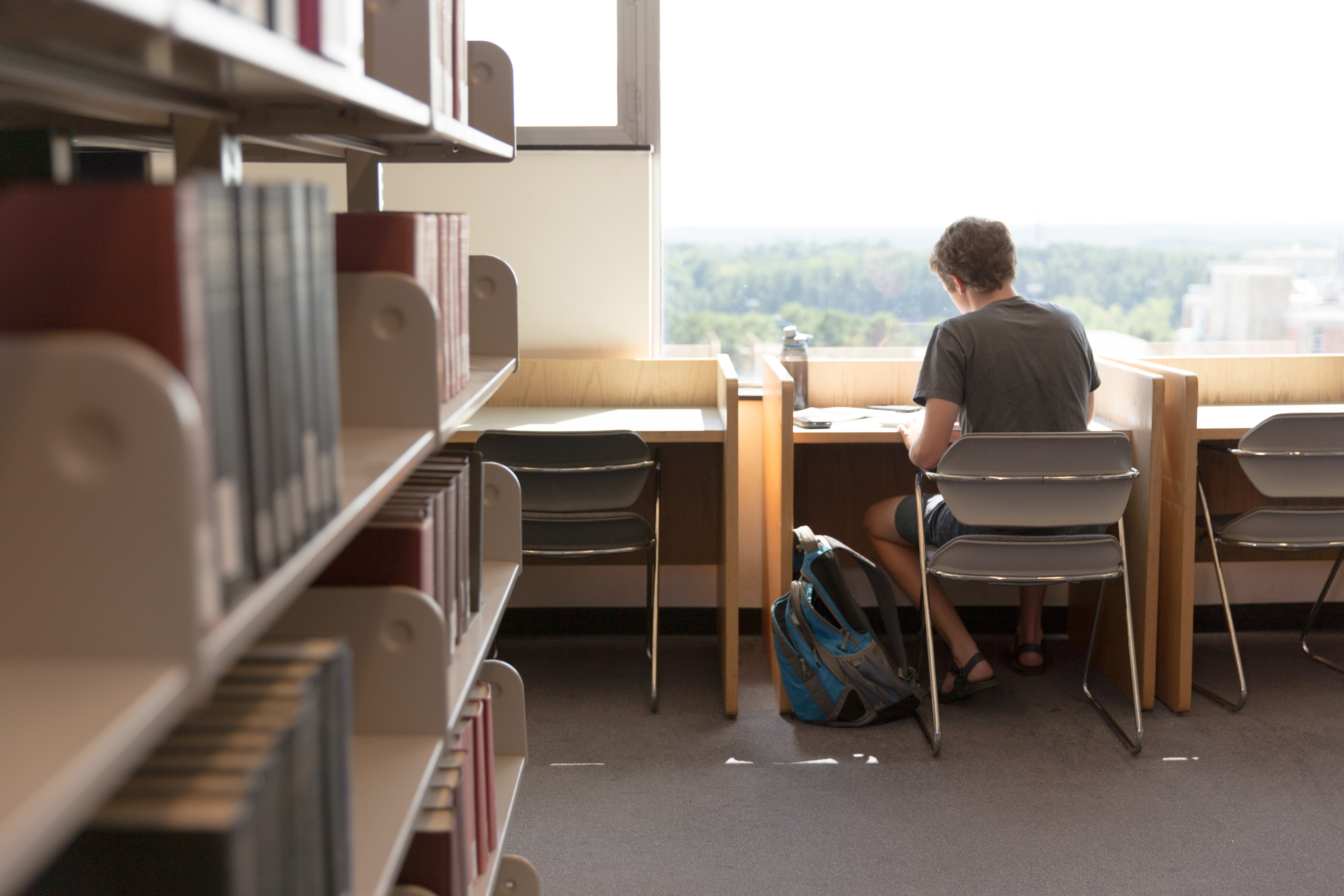 A student sits at a desk on the second floor bookstacks