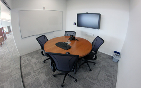 A room with a whiteboard, table, chairs, and wall mounted screen