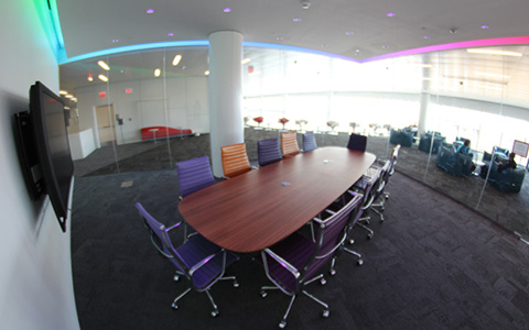 A glass walled room with a conference table and wall mounted screen.