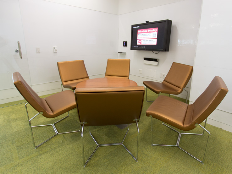A graduate study lounge at Hunt Library with a low table and chairs and a wall mounted screen