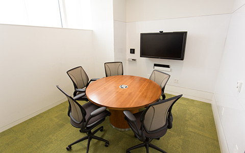 A graduate study room at Hunt Library with a wall mounted screen, table, and chairs