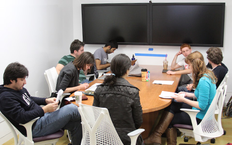 Students sitting around a table in a large group study room with double mounted monitors on one wall at Hunt Library