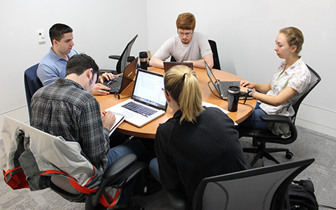 Students sitting at a round table working on laptops in a medium group study room at Hunt Library