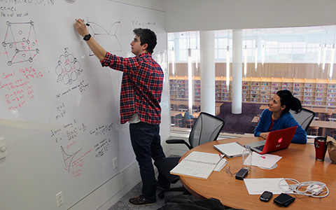 Students working on a whiteboard in a small study room with one glass wall