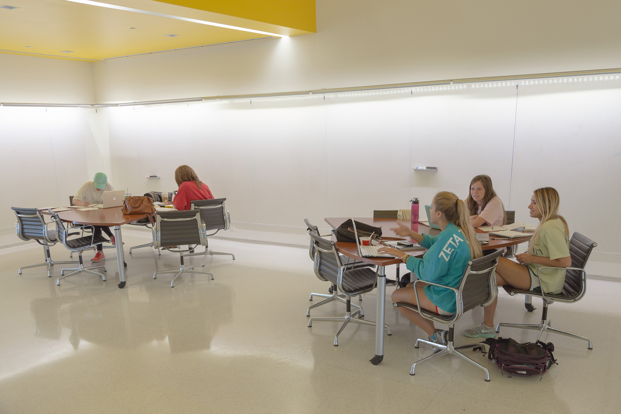 Students work at tables surrounded by white board walls in the idea alcove