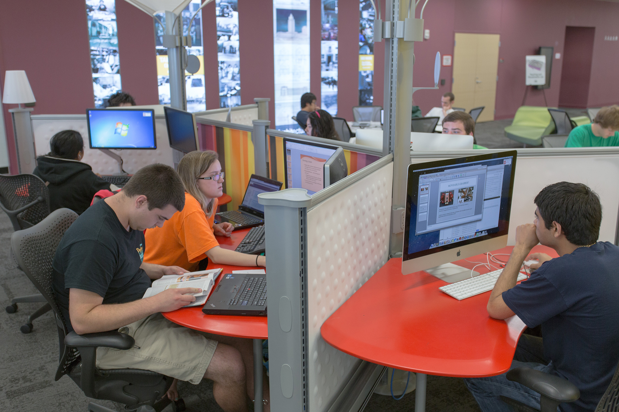 Students working at three computer workstations on double monitors