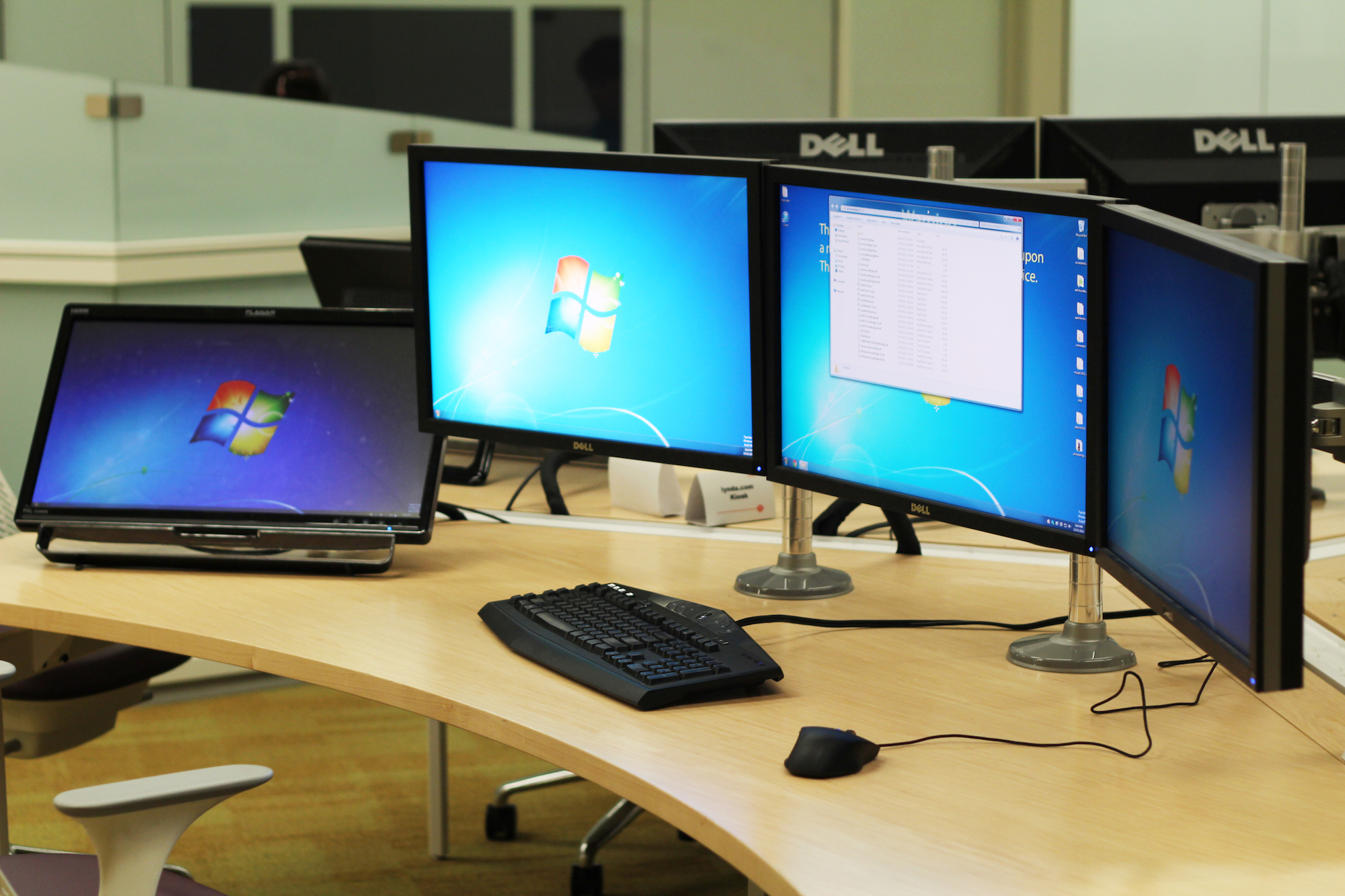 A programming workstation with keyboard, mouse, and four screens at Hunt Library