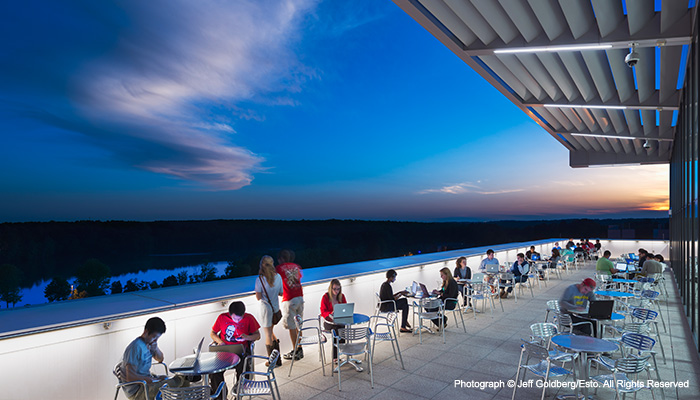 Students working at small tables outdoors on the skyline terrace at hunt library with the sun setting over lake raleigh in the background