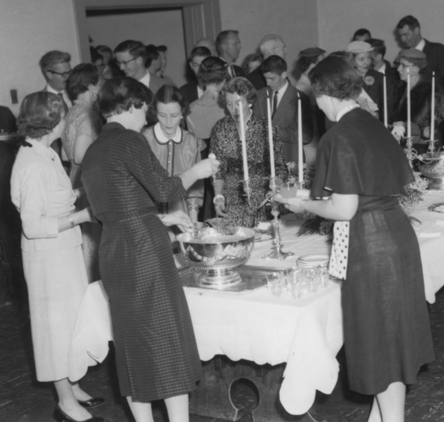A crowd gathers around the punch bowl, ca. 1950.