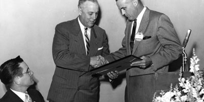 1957: LeRoy Martin receives award of merit from State College foundation director L. L. Roy, with president William C. Friday looking on Alumni Weekend.