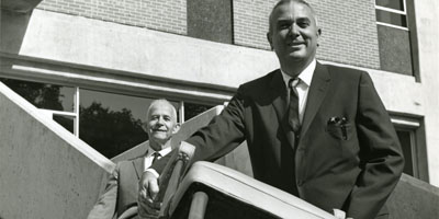 "1964: Arthur Clayton ""Buck"" Menius (right), the first dean of the School of Physical Sciences and Applied Mathematics, and Associate Dean Raymond Stainback moving in to Cox Hall."